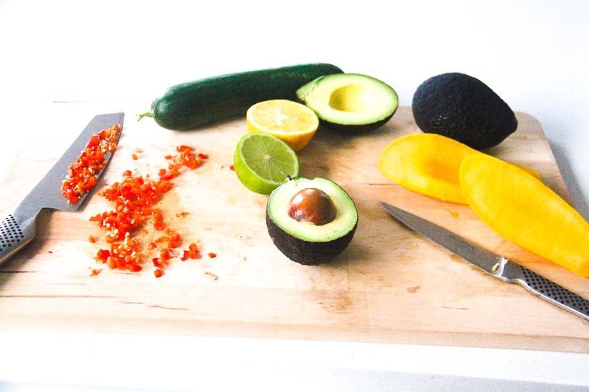 A board full of Ingredients primed for making homemade Fresh Mango Guacamole. Image © Skye Gilkeson