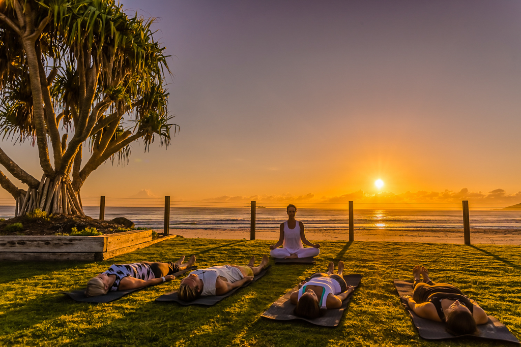 Guests asana with the sunrise at the beach at Elements of Byron. Image © Skye Gilkeson