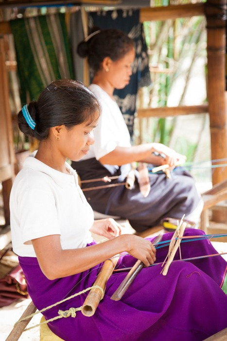 Local women weaving Ikat Textiles native to Sumba Island. Image © Ken Kochey